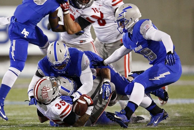 Nov 21, 2013; Colorado Springs, CO, USA; UNLV Rebels running back Tim Cornett (35) is tackled by Air Force Falcons defensive lineman David Harris (53) in the second quarter at Falcon Stadium. Mandatory Credit: Isaiah J. Downing-USA TODAY Sports