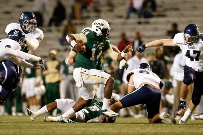 Nov 21, 2013; Birmingham, AL, USA; UAB Blazers quarterback Jonathan Perry (14) carries the ball against the Rice Owls at Legion Field. The Owls defeated the Blazers 37-34 in overtime. Mandatory Credit: Marvin Gentry-USA TODAY Sports