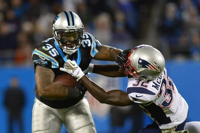 Nov 18, 2013; Charlotte, NC, USA; Carolina Panthers fullback Mike Tolbert (35) runs as New England Patriots free safety Devin McCourty (32) defends in the third quarter. The Panthers defeated the Patriots 24-20 at Bank of America Stadium. Mandatory Credit: Bob Donnan-USA TODAY Sports