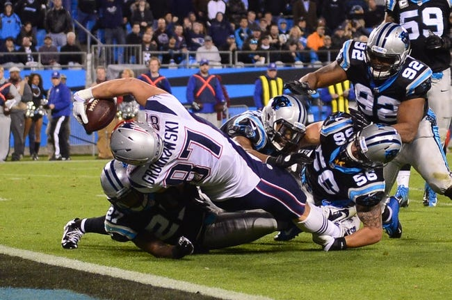 Nov 18, 2013; Charlotte, NC, USA; New England Patriots tight end Rob Gronkowski (87) scores a touchdown as Carolina Panthers free safeties Mike Mitchell (21) and  Quintin Mikell (27) and inside linebacker A.J. Klein (56) and defensive tackle Dwan Edwards (92) defend in the third quarter. The Panthers defeated the Patriots 24-20 at Bank of America Stadium. Mandatory Credit: Bob Donnan-USA TODAY Sports
