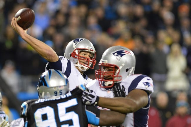 Nov 18, 2013; Charlotte, NC, USA; New England Patriots quarterback Tom Brady (12) passes the ball as tackle Marcus Cannon (61) blocks and Carolina Panthers defensive end Charles Johnson (95) defends in the fourth quarter. The Panthers defeated the Patriots 24-20 at Bank of America Stadium. Mandatory Credit: Bob Donnan-USA TODAY Sports