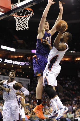 Nov 22, 2013; Charlotte, NC, USA; Charlotte Bobcats guard Kemba Walker (15) drives to the basket as he is defended by Phoenix Suns center Alex Len (21) during the second half of the game at Time Warner Cable Arena. Suns win 98-91.  Mandatory Credit: Sam Sharpe-USA TODAY Sports