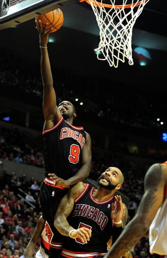 Nov 22, 2013; Portland, OR, USA; Chicago Bulls small forward Luol Deng (9) lays the ball in over Chicago Bulls power forward Carlos Boozer (5) during the first quarter of the game against the Portland Trail Blazers at the Moda Center. Mandatory Credit: Steve Dykes-USA TODAY Sports