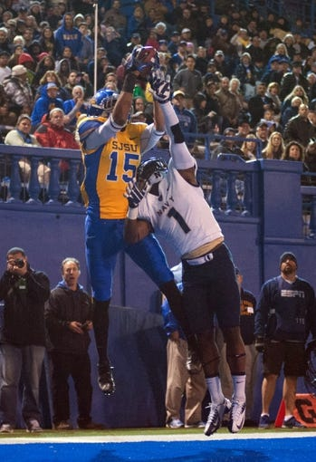 Nov 22, 2013; San Jose, CA, USA; San Jose State Spartans wide receiver Tyler Winston (15) catches a touchdown pass against Navy Midshipmen cornerback Brendon Clements (1) during the fourth quarter at Spartan Stadium. Navy won 58-52 in triple overtime. Mandatory Credit: Ed Szczepanski-USA TODAY Sports