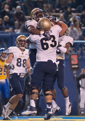 Nov 22, 2013; San Jose, CA, USA; Navy Midshipmen running back Darius Staten (20) celebrates with center Blaze Ryder (63) after scoring a touchdown against the San Jose State Spartans at Spartan Stadium. Navy won 58-52 in triple overtime. Mandatory Credit: Ed Szczepanski-USA TODAY Sports