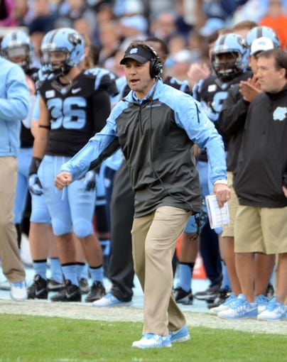 Nov 23, 2013; Chapel Hill, NC, USA; North Carolina Tar Heels head coach Larry Fedora (center) cheers a defensive stop against the Old Dominion Monarchs during the first half at Kenan Memorial Stadium. Mandatory Credit: Rob Kinnan-USA TODAY Sports