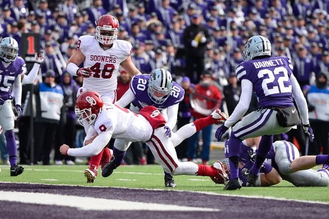 Nov 23, 2013; Manhattan, KS, USA; Oklahoma Sooners quarterback Trevor Knight (9) scores a touchdown against the Kansas State Wildcats during the first half at Bill Snyder Family Stadium. Mandatory Credit: Jasen Vinlove-USA TODAY Sports