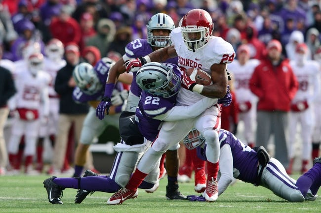 Nov 23, 2013; Manhattan, KS, USA; Oklahoma Sooners running back Brennan Clay (24) is tackled by Kansas State Wildcats defensive back Dante Barnett (22) during the first half at Bill Snyder Family Stadium. Mandatory Credit: Jasen Vinlove-USA TODAY Sports