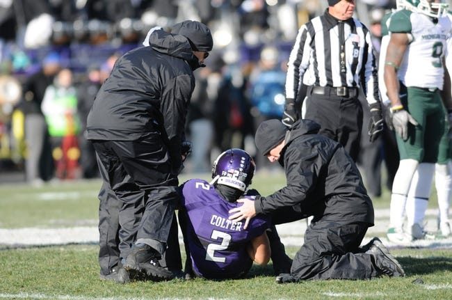 Nov 23, 2013; Evanston, IL, USA; Northwestern Wildcats quarterback Kain Colter (2) is helped off the field during the first quarter against the Michigan State Spartans at Ryan Field. Michigan State Spartans safety Isaiah Lewis (9) was ejected from the game for the targeting hit. Mandatory Credit: Reid Compton-USA TODAY Sports