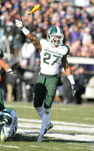 Nov 23, 2013; Evanston, IL, USA; Michigan State Spartans safety Kurtis Drummond (27) signals for a turnover as a penalty flag flies behind him. Safety Isaiah Lewis (9) was ejected from the game on the play for a personal foul against Northwestern Wildcats quarterback Kain Colter (2) at Ryan Field. Mandatory Credit: Reid Compton-USA TODAY Sports