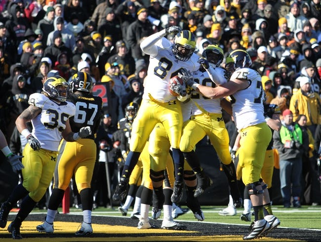 Nov 23, 2013; Iowa City, IA, USA;  Michigan Wolverines tight end  A.J. Williams (84) celebrates with teammates Fitzgerald Toussaint (28) and Michael Schofield (75) against the Iowa Hawkeyes at Kinnick Stadium. Mandatory Credit: Reese Strickland-USA TODAY Sports