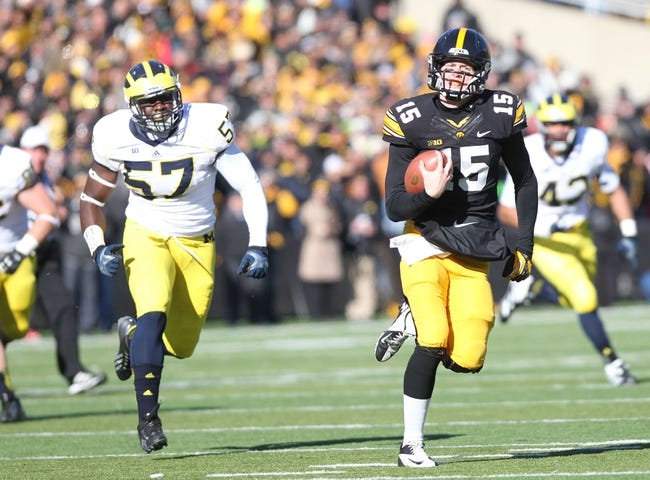 Nov 23, 2013; Iowa City, IA, USA; Iowa Hawkeyes quarterback Jake Rudock (15) runs away from  Michigan Wolverines defensive end Frank Clark (57) at Kinnick Stadium. Mandatory Credit: Reese Strickland-USA TODAY Sports