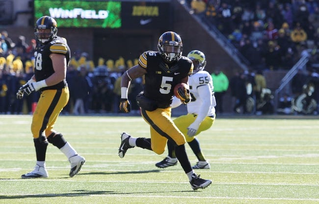 Nov 23, 2013; Iowa City, IA, USA; Iowa Hawkeyes running back Damon Bullock (5) runs the football against the Michigan Wolverines at Kinnick Stadium. Mandatory Credit: Reese Strickland-USA TODAY Sports