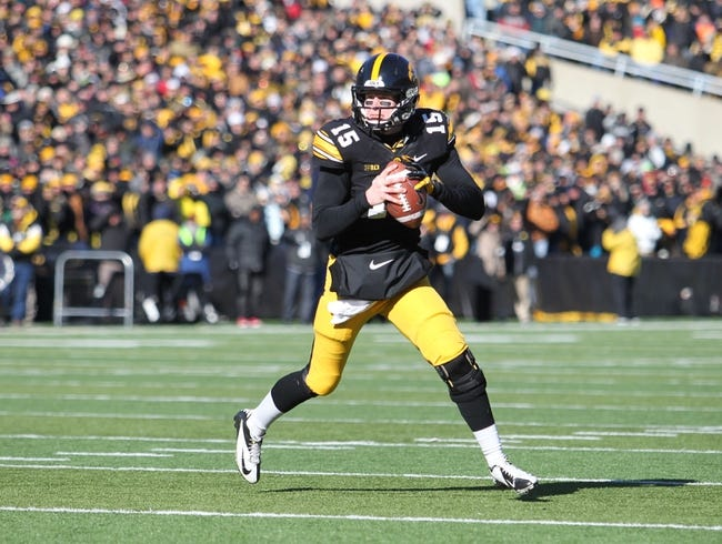 Nov 23, 2013; Iowa City, IA, USA; Iowa Hawkeyes quarterback Jake Rudock (15) rolls out to pass against the Michigan Wolverines at Kinnick Stadium. Mandatory Credit: Reese Strickland-USA TODAY Sports
