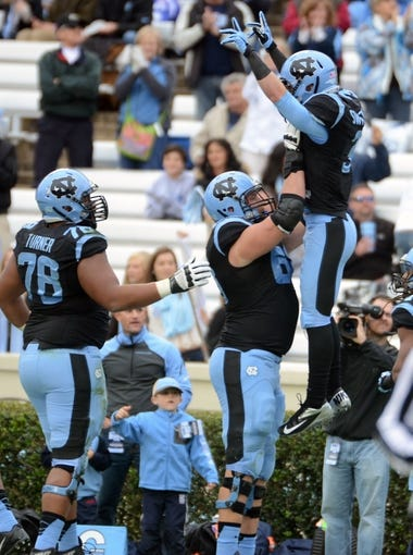 Nov 23, 2013; Chapel Hill, NC, USA; North Carolina Tar Heels receiver Ryan Swisher (right) celebrates a first half touchdown against the Old Dominion Monarchs with teammate James Hurst (68) during the first half at Kenan Memorial Stadium. Mandatory Credit: Rob Kinnan-USA TODAY Sports