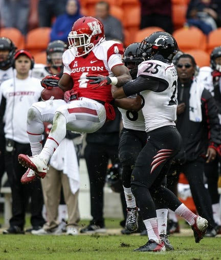 Nov 23, 2013; Houston, TX, USA; Houston Cougars wide receiver Daniel Spencer (4) attempts to make a catch during the second quarter as Cincinnati Bearcats safety Arryn Chenault (25) defends at BBVA Compass Stadium. Mandatory Credit: Troy Taormina-USA TODAY Sports