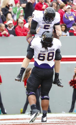 Nov 23, 2013; Raleigh, NC, USA; East Carolina Pirates quarterback Shane Carden (5) is lifted into the air by teammate offensive linemen Tre Robertson (68) after his 2nd quarter touchdown run against the North Carolina State Wolfpack at Carter Finley Stadium. Mandatory Credit: James Guillory-USA TODAY Sports