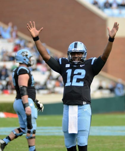 Nov 23, 2013; Chapel Hill, NC, USA; North Carolina Tar Heels quarterback Marquise Williams (12) signals touchdown during a reviewed play during the second half against the Old Dominion Monarchs at Kenan Memorial Stadium. The Tar Heels won 80-20.  Mandatory Credit: Rob Kinnan-USA TODAY Sports