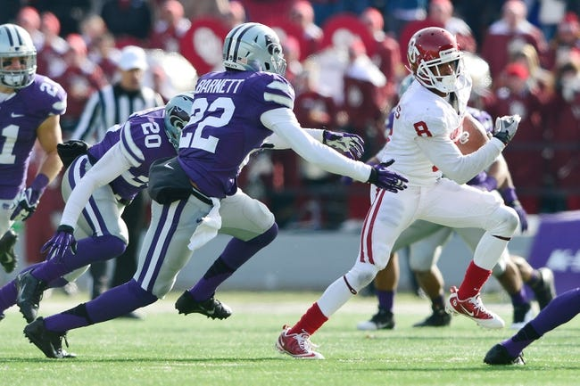 Nov 23, 2013; Manhattan, KS, USA; Oklahoma Sooners wide receiver Jalen Saunders (8) runs the ball as Kansas State Wildcats defensive back Dante Barnett (22) defends during the second half at Bill Snyder Family Stadium. The Sooners won 41-31. Mandatory Credit: Jasen Vinlove-USA TODAY Sports