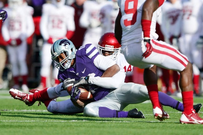 Nov 23, 2013; Manhattan, KS, USA; Kansas State Wildcats wide receiver Lucas Munds (10) is tackled by Oklahoma Sooners defensive back Aaron Colvin (14) during the second half at Bill Snyder Family Stadium. The Sooners won 41-31. Mandatory Credit: Jasen Vinlove-USA TODAY Sports