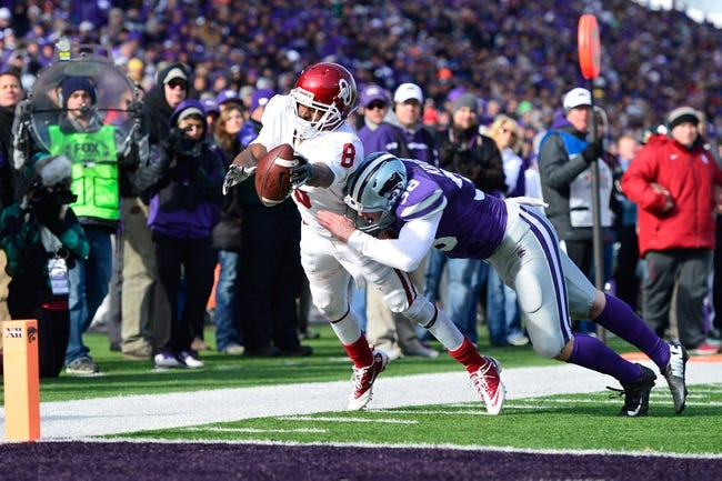 Nov 23, 2013; Manhattan, KS, USA; Oklahoma Sooners wide receiver Jalen Saunders (8) is tackled out of bounds by Kansas State Wildcats punter Mark Krause (38) during the second half at Bill Snyder Family Stadium. The Sooners won 41-31. Mandatory Credit: Jasen Vinlove-USA TODAY Sports