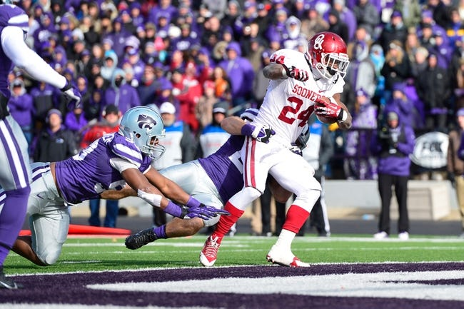 Nov 23, 2013; Manhattan, KS, USA; Oklahoma Sooners running back Brennan Clay (24) scores a touchdown against the Kansas State Wildcats during the second half at Bill Snyder Family Stadium. The Sooners won 41-31. Mandatory Credit: Jasen Vinlove-USA TODAY Sports