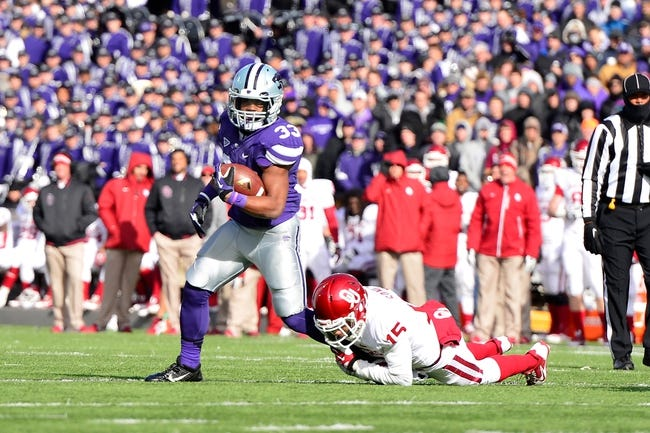 Nov 23, 2013; Manhattan, KS, USA; Kansas State Wildcats running back John Hubert (33) is tackled by Oklahoma Sooners defensive back Zack Sanchez (15) during the second half at Bill Snyder Family Stadium. The Sooners won 41-31. Mandatory Credit: Jasen Vinlove-USA TODAY Sports