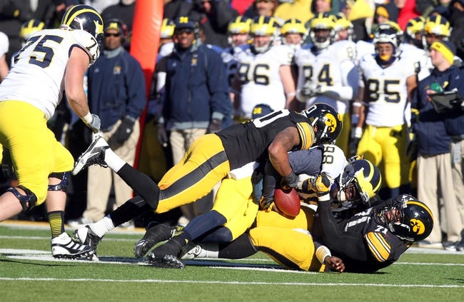 Nov 23, 2013; Iowa City, IA, USA; Michigan Wolverines quarterback Devin Gardner (98) is sacked by Iowa Hawkeyes linebacker Christian Kirksey (20) and left tackle Carl Davis (71) at Kinnick Stadium. Iowa beat Michigan 24-21.  Mandatory Credit: Reese Strickland-USA TODAY Sports