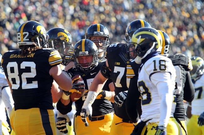 Nov 23, 2013; Iowa City, IA, USA;  Iowa Hawkeyes running back Mark Weisman (45) is congratulated by teammates after scoring a touchdown against the Michigan Wolverines at Kinnick Stadium. Iowa beat Michigan 24-21.  Mandatory Credit: Reese Strickland-USA TODAY Sports