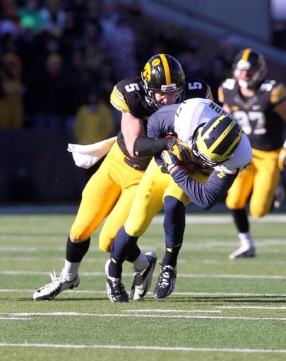 Nov 23, 2013; Iowa City, IA, USA;  Michigan Wolverines wide receiver Jeremy Jackson (17) is tackled after the catch by Iowa Hawkeyes safety Tanner Miller (5) at Kinnick Stadium. Iowa beat Michigan 24-21.  Mandatory Credit: Reese Strickland-USA TODAY Sports
