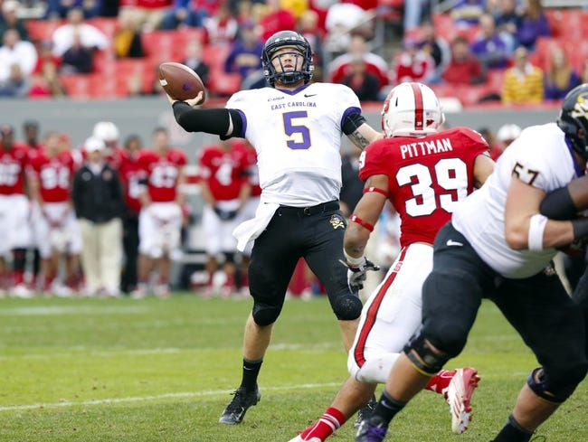 Nov 23, 2013; Raleigh, NC, USA; East Carolina Pirates quarterback Shane Carden (5) throws a 4th quarter touchdown pass against the North Carolina State Wolfpack at Carter Finley Stadium. The East Carolina Pirates defeated the North Carolina State Wolfpack 42-28. Mandatory Credit: James Guillory-USA TODAY Sports