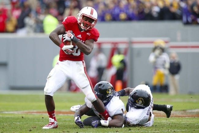 Nov 23, 2013; Raleigh, NC, USA; North Carolina State Wolfpack running back Shadrach Thornton gets past East Carolina Pirates defensive back Chip Thompson (1) and linebacker Gabe Woullard (42) during the 3rd quarter at Carter Finley Stadium. The East Carolina Pirates defeated the North Carolina State Wolfpack 42-28. Mandatory Credit: James Guillory-USA TODAY Sports