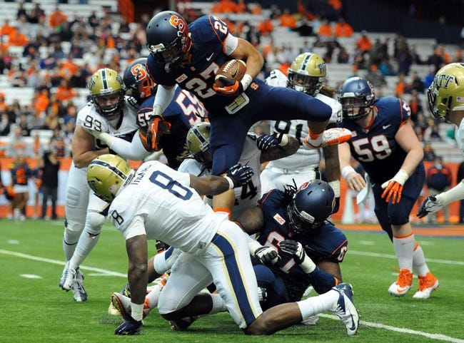Nov 23, 2013; Syracuse, NY, USA; Syracuse Orange running back George Morris II (27) leaps over the tackle attempt of Pittsburgh Panthers linebacker Todd Thomas (8) during the fourth quarter at the Carrier Dome.  Pittsburgh defeated Syracuse 17-16.  Mandatory Credit: Rich Barnes-USA TODAY Sports