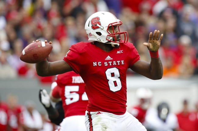 Nov 23, 2013; Raleigh, NC, USA; North Carolina State Wolfpack quarterback Brandon Mitchell (8) throws the ball against he East Carolina Pirates at Carter Finley Stadium. The East Carolina Pirates defeated the North Carolina State Wolfpack 42-28. Mandatory Credit: James Guillory-USA TODAY Sports