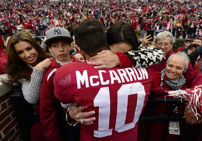 Nov 23, 2013; Tuscaloosa, AL, USA; Alabama Crimson Tide quarterback A.J. McCarron (10) stops to hug his mother Dee Dee Bonner as he made a victory lap around the stadium after their 49-0 win over the Chattanooga Mocs at Bryant-Denny Stadium. This was McCarron's final home game of his senior year. Katherine Webb the girlfriend of McCarron is seen far left. Mandatory Credit: John David Mercer-USA TODAY Sports