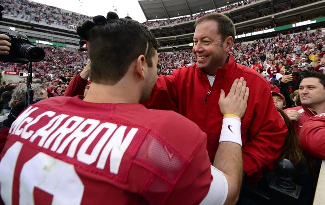 Nov 23, 2013; Tuscaloosa, AL, USA; Alabama Crimson Tide quarterback A.J. McCarron (10) stops to greet his father Tony McCarron as he made a victory lap around the stadium after their 49-0 win over the Chattanooga Mocs at Bryant-Denny Stadium. This was McCarron's final home game of his senior year. Mandatory Credit: John David Mercer-USA TODAY Sports