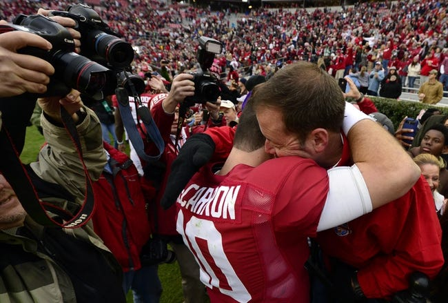 Nov 23, 2013; Tuscaloosa, AL, USA; Alabama Crimson Tide quarterback A.J. McCarron (10) stops to hug his father Tony McCarron as he made a victory lap around the stadium after their 49-0 win over the Chattanooga Mocs at Bryant-Denny Stadium. This was McCarron's final home game of his senior year. Mandatory Credit: John David Mercer-USA TODAY Sports