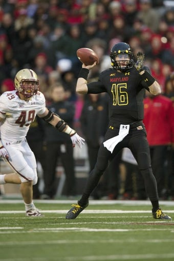 Nov 23, 2013; College Park, MD, USA;  Maryland Terrapins quarterback C.J. Brown (16) throws the ball as Boston College Eagles linebacker Steele Divitto (49) chases him from behind during the first half at Byrd Stadium. Mandatory Credit: Tommy Gilligan-USA TODAY Sports