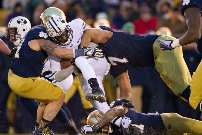 Nov 23, 2013; South Bend, IN, USA; BYU Cougars running back Jamaal Williams (21) is tackled by Notre Dame Fighting Irish linebacker Carlo Calabrese (44) and defensive end Stephon Tuitt (7) in the second quarter at Notre Dame Stadium. Mandatory Credit: Matt Cashore-USA TODAY Sports