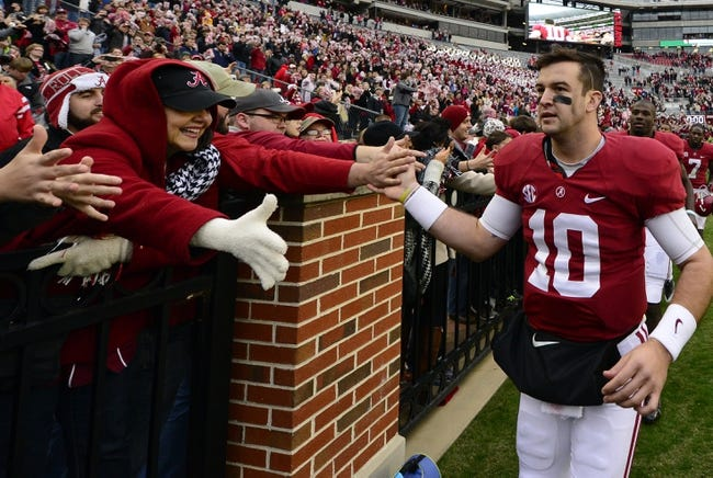 Nov 23, 2013; Tuscaloosa, AL, USA; Alabama Crimson Tide quarterback A.J. McCarron (10) celebrates by making a victory lap around the stadium after their 49-0 win over the Chattanooga Mocs at Bryant-Denny Stadium. This was McCarron's final home game of his senior year. Mandatory Credit: John David Mercer-USA TODAY Sports