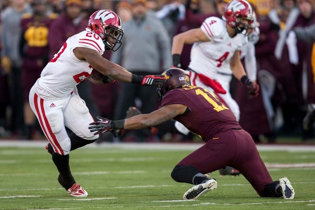 Nov 23, 2013; Minneapolis, MN, USA; Wisconsin Badgers running back James White (20) rushes with the ball around Minnesota Golden Gophers defensive back Antonio Johnson (11) in the second quarter at TCF Bank Stadium. Mandatory Credit: Jesse Johnson-USA TODAY Sports
