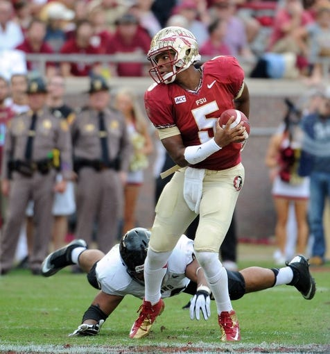 Nov 23, 2013; Tallahassee, FL, USA; Florida State Seminoles quarterback Jameis Winston (5) gets away from Idaho Vandals defensive end Maxx Forde (40) during the first half at Doak Campbell Stadium. Mandatory Credit: Melina Vastola-USA TODAY Sports
