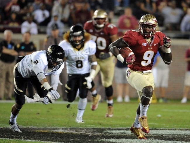Nov 23, 2013; Tallahassee, FL, USA; Florida State Seminoles running back Karlos Williams (9) runs past Idaho Vandals safety Bradley Njoku (2) during the second half at Doak Campbell Stadium. Mandatory Credit: Melina Vastola-USA TODAY Sports