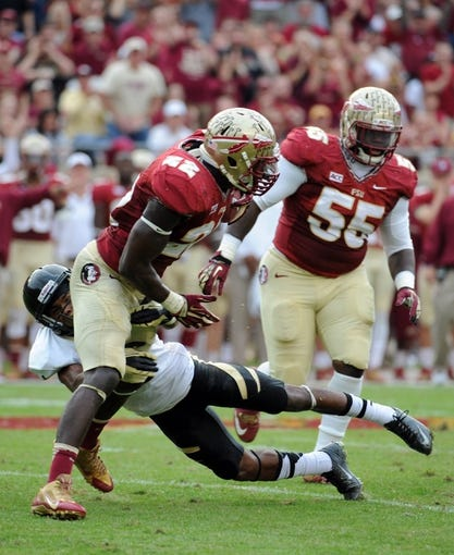 Nov 23, 2013; Tallahassee, FL, USA; Florida State Seminoles linebacker Telvin Smith (22) gets away from a tackle by Idaho Vandals wide receiver Dezmon Epps (1) after an interception during the first half at Doak Campbell Stadium. Mandatory Credit: Melina Vastola-USA TODAY Sports