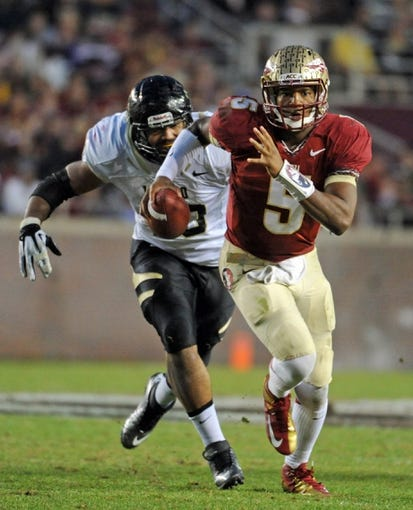 Nov 23, 2013; Tallahassee, FL, USA; Florida State Seminoles quarterback Jameis Winston (5) runs away from pressure by Idaho Vandals defensive end Maxx Forde (40) during the second half at Doak Campbell Stadium. Mandatory Credit: Melina Vastola-USA TODAY Sports