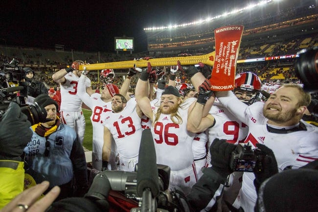 Nov 23, 2013; Minneapolis, MN, USA; Wisconsin Badgers team hold up the Paul Bunyan Axe after defeating the Minnesota Golden Gophers at TCF Bank Stadium. The Badgers won 20-7. Mandatory Credit: Jesse Johnson-USA TODAY Sports