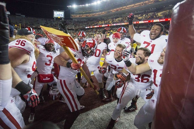 Nov 23, 2013; Minneapolis, MN, USA; Wisconsin Badgers kicker Jack Russell (97) chops down the goal post with the Paul Bunyon Axe after defeating the Minnesota Golden Gophers at TCF Bank Stadium. The Badgers won 20-7. Mandatory Credit: Jesse Johnson-USA TODAY Sports