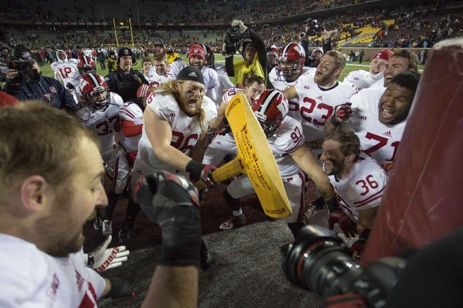 Nov 23, 2013; Minneapolis, MN, USA; Wisconsin Badgers nose tackle Beau Allen (96) chops down the goal post with the Paul Bunyon Axe after defeating the Minnesota Golden Gophers at TCF Bank Stadium. THe Badgers won 20-7. Mandatory Credit: Jesse Johnson-USA TODAY Sports