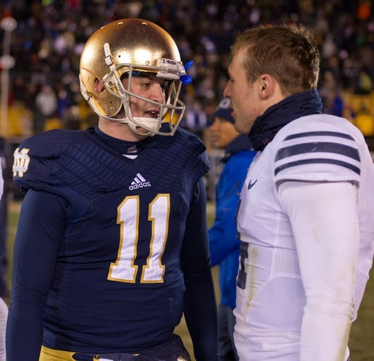 Nov 23, 2013; South Bend, IN, USA; Notre Dame Fighting Irish quarterback Tommy Rees (11) talks with BYU Cougars quarterback Taysom Hill (4) after Notre Dame defeated the Cougars 23-13 at Notre Dame Stadium. Mandatory Credit: Matt Cashore-USA TODAY Sports