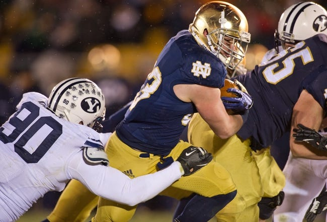 Nov 23, 2013; South Bend, IN, USA; Notre Dame Fighting Irish running back Cam McDaniel (33) carries the ball as BYU Cougars defensive lineman Bronson Kaufusi (90) defends in the third quarter at Notre Dame Stadium. Notre Dame won 23-13. Mandatory Credit: Matt Cashore-USA TODAY Sports